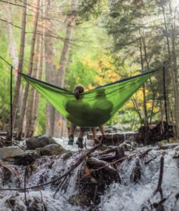 Women in a hammock in the forest.